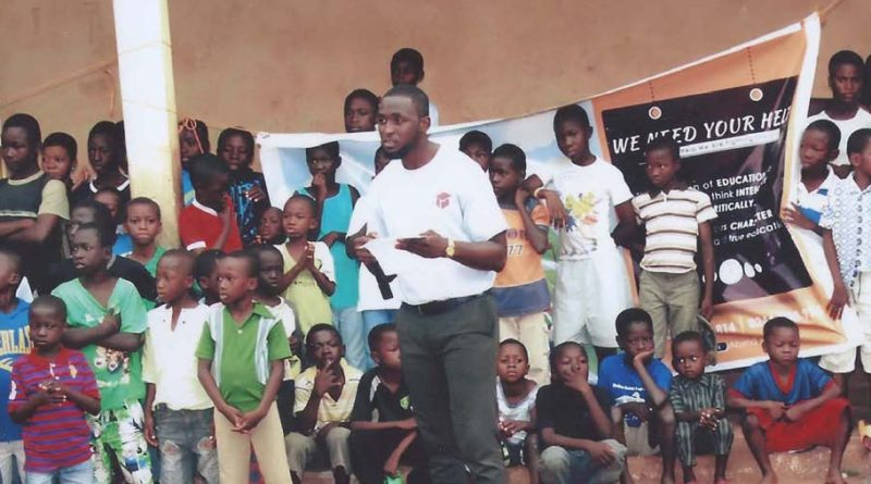 Housing Assistant Thomas Osei with children in front of a library he raised funds to build in Kumasi, Ghana, so that children could have books and encouragement to succeed in school.
