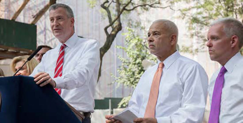 Mayor Bill de Blasio announces the start of the $87 Million Queensbridge Houses roof replacement. To his right are General Manager Michael Kelly and City councilmember Jimmy Van Bramer.